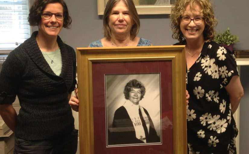 Pictured above: Photo of Rev. Joyce Stedge held by Debbie Stedge, standing with Rev. Amy Nyland and Rev. Julia Doellman-Brown